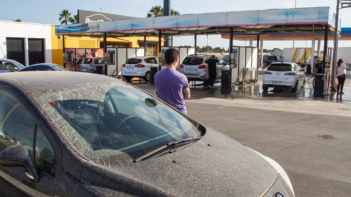 Un conductor espera su turno para lavar el coche tras caerle encima la lluvia de barro