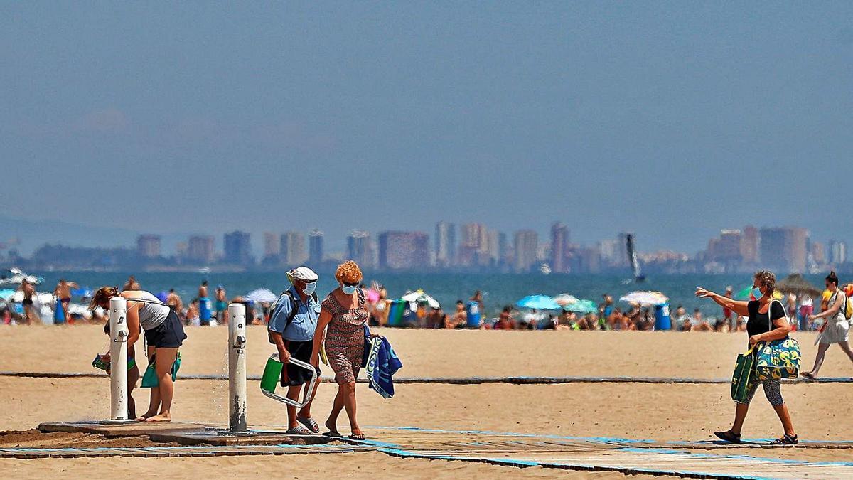 Un grupo abandona la playa de Las Arenas de València durante el pasado verano. | EFE