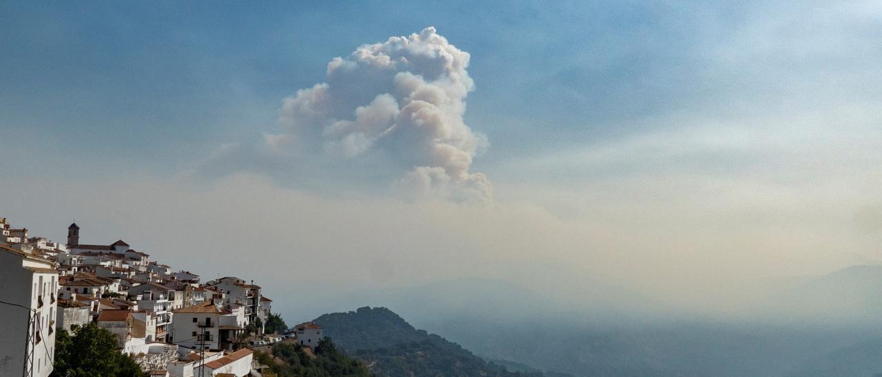 Vista del pueblo de Algatocín junto a una nube de humo que proviene del incendio declarado en Jubrique.