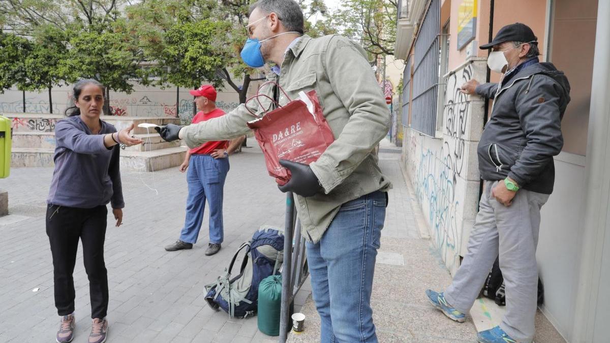Un policía de paisano reparte mascarillas entre personas sin hogar.