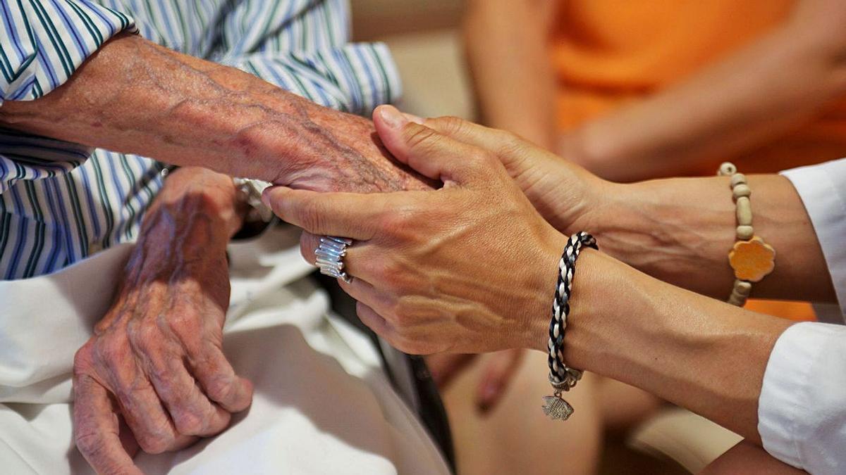 Una auxiliar de ayuda a domiclio, con una persona mayor. |   // EUROPA PRESS