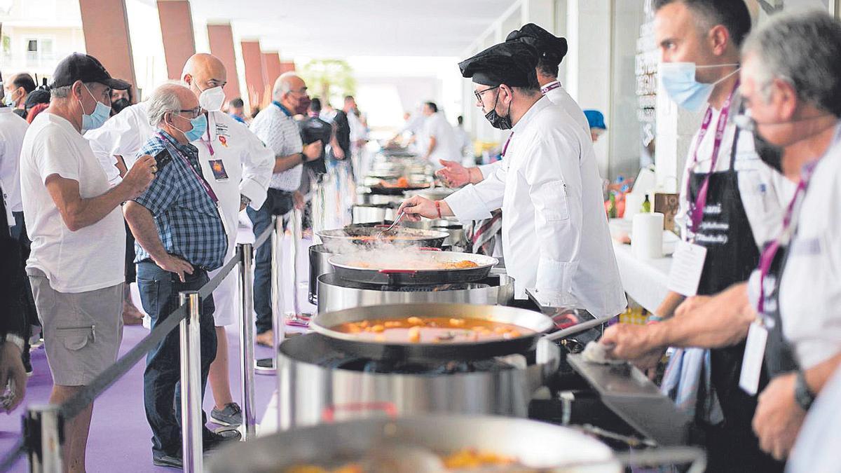 Un momento de la elaboración de las fideuaes por parte de los chefs inscritos y, a la derecha, el alcalde con el dueño y la cocinera del restaurante Casa Granero de Serra.