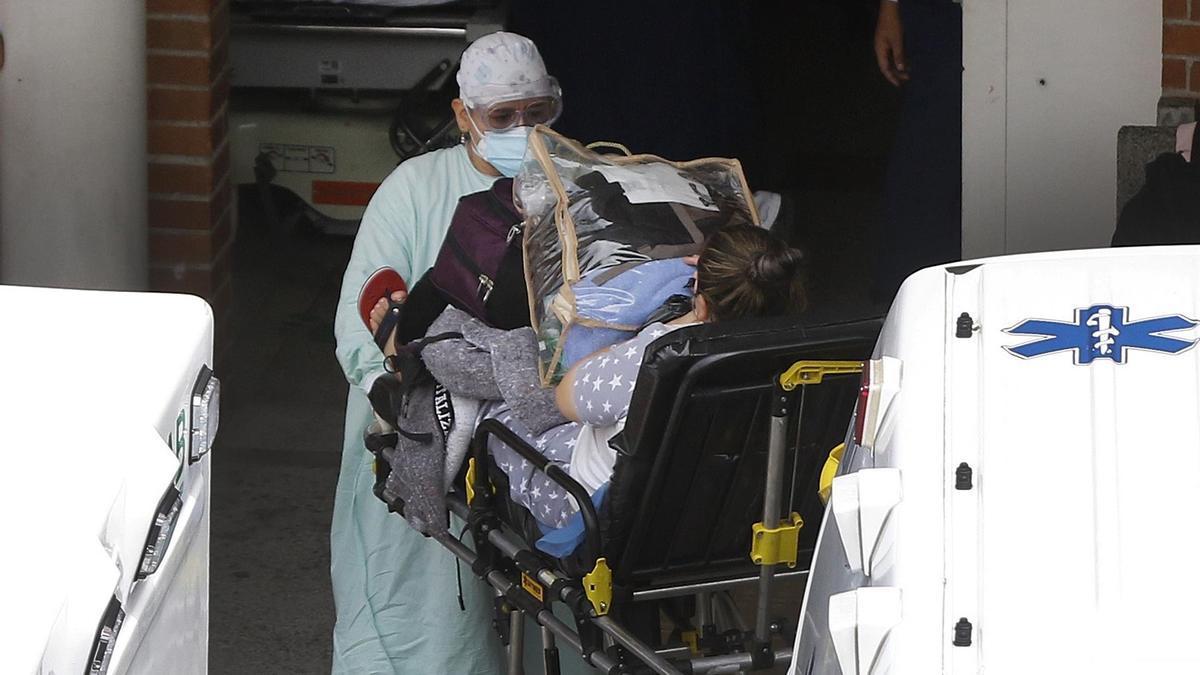 Personal sanitario transporta a una paciente covid-19
