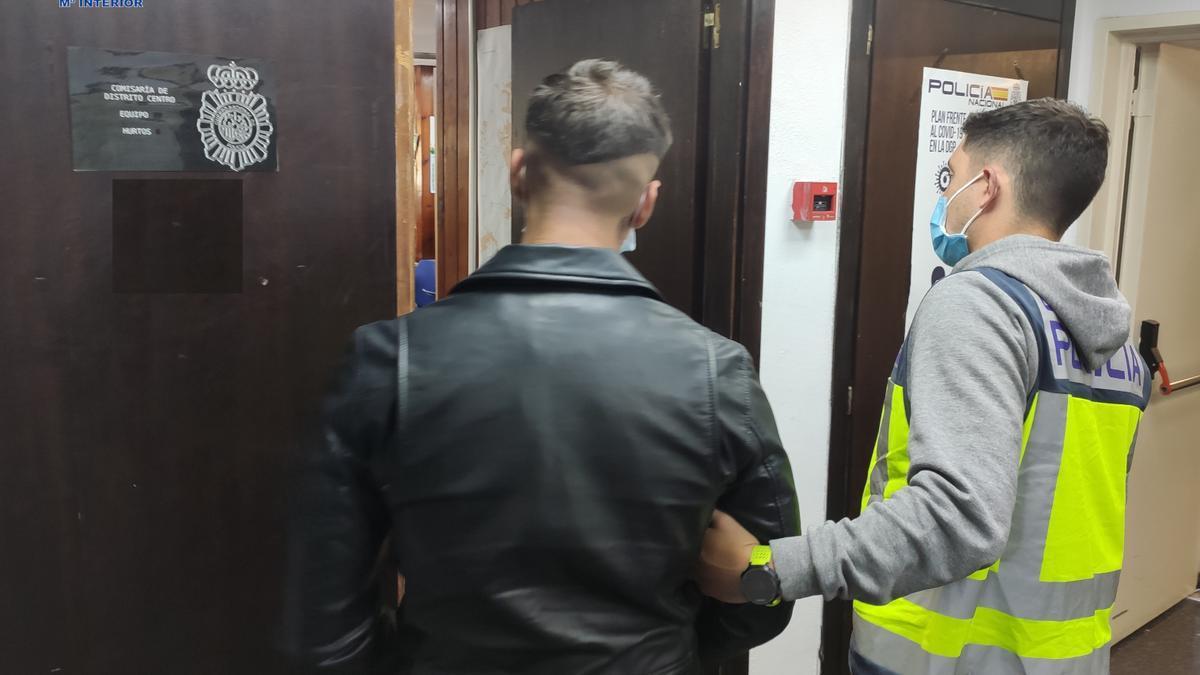 Un agente lleva detenido al asaltante que dio un puñetazo a la víctima.