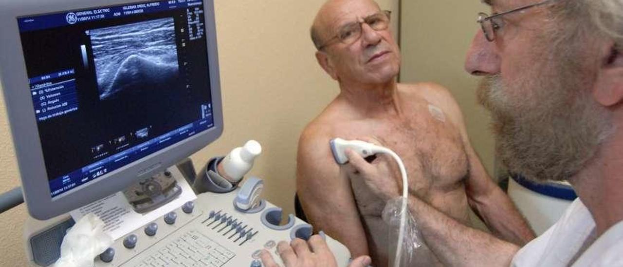 Un médico, realizando una ecografía a un paciente en el centro de salud de Sotrondio en 2014.