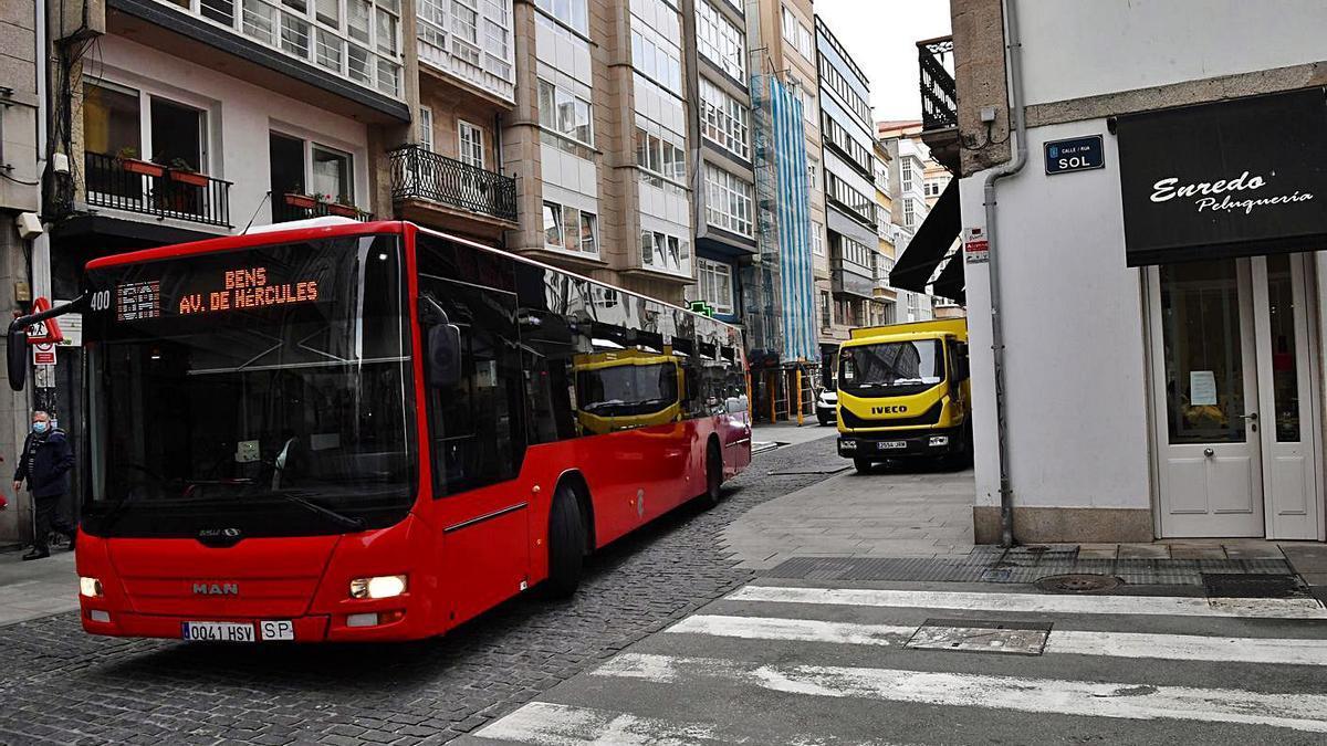 Un autobús a punto de girar hacia la calle Sol con un camión aparcado en la acera.   | // CARLOS PARDELLAS