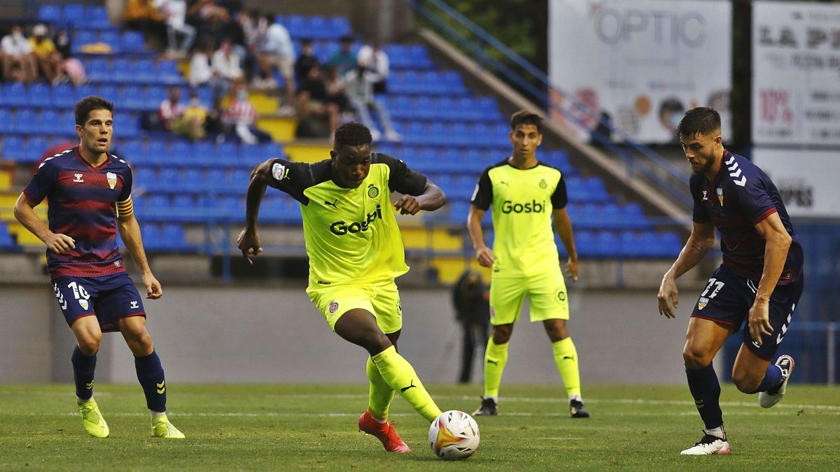 Ibrahima Kébé condueix la pilota davant la mirada    de Guiu i Gil.  