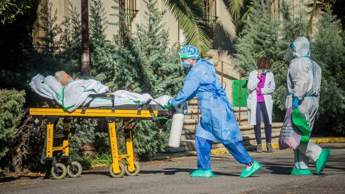 Una celadora traslada al hospital a un enfermo de covid.