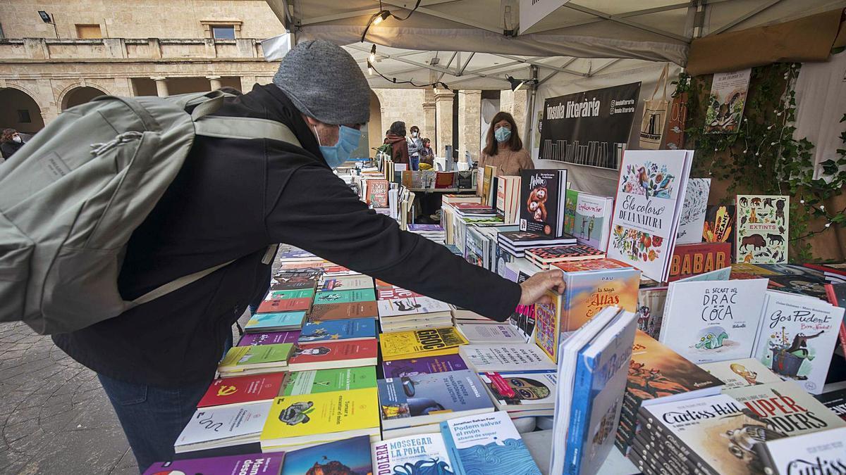 Un lector se interesa por un volumen expuesto en la Setmana del Llibre en Català.