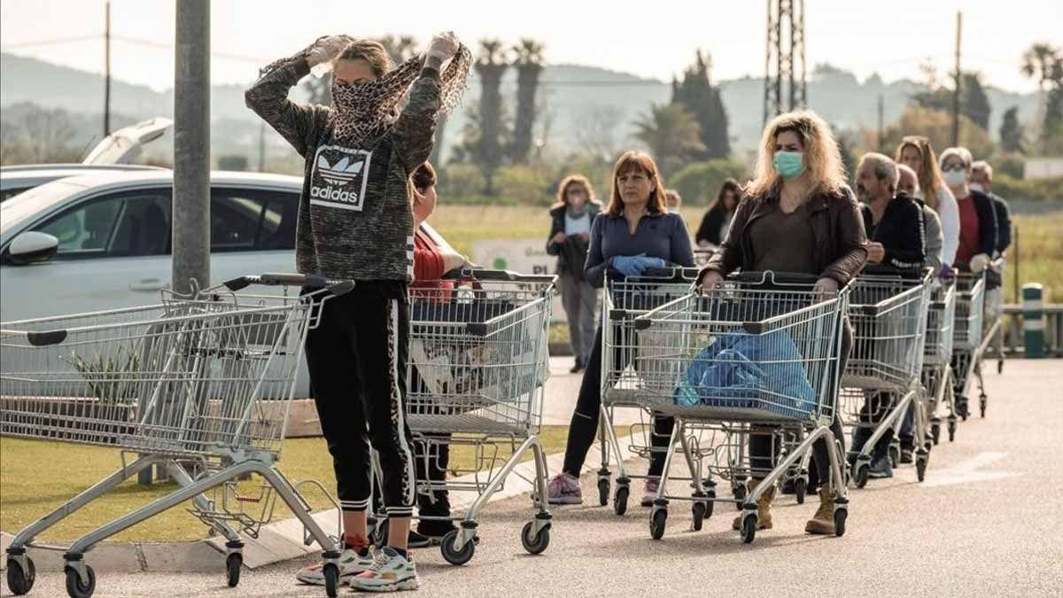 Varias personas esperan para hacer la compra