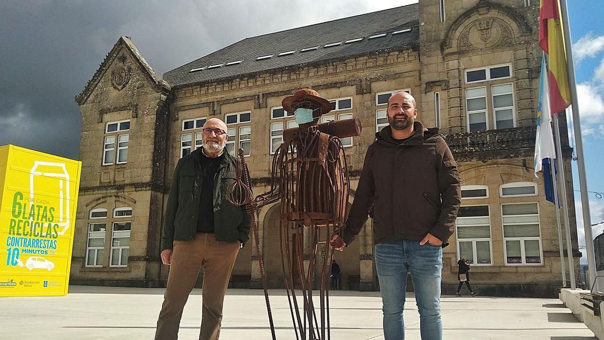 Manuel Lago Román y su hijo Xoán posan junto al peregrino metálico frente al consistorio.  | // L.D.