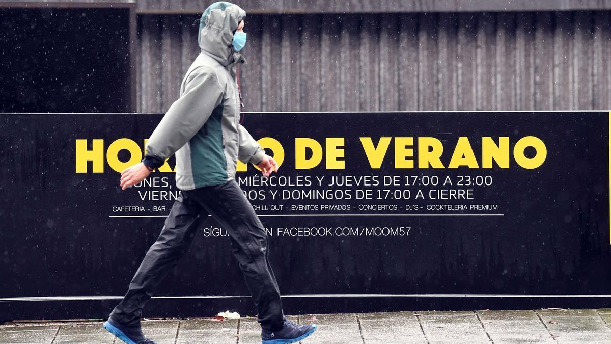 Un joven con capucha pasa junto a un cartel con la leyenda 'horario de verano' en A Coruña.