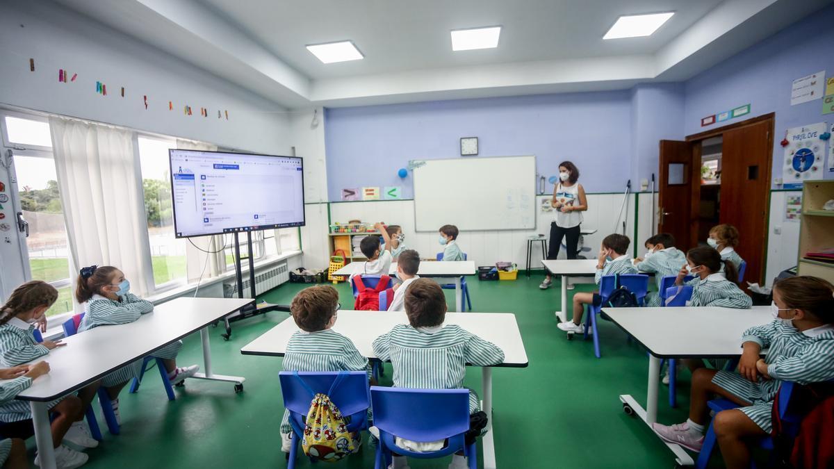 Varios niños escuchan las explicaciones de su profesora en una clase.