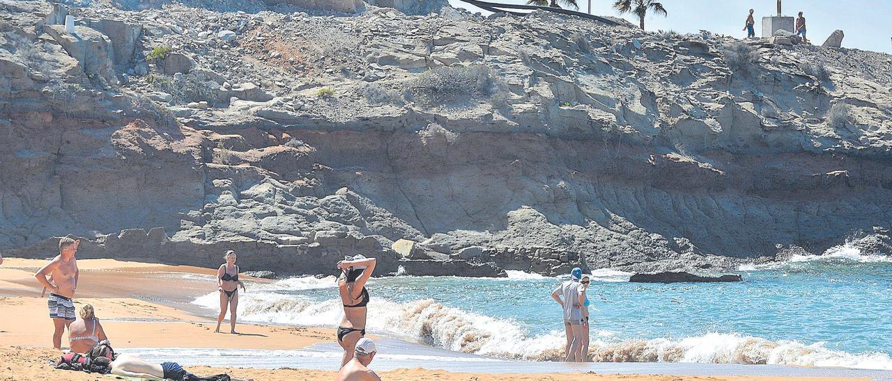 Bañistas en la playa de Tauro al poco de colocar Anfi la arena del Sáhara.