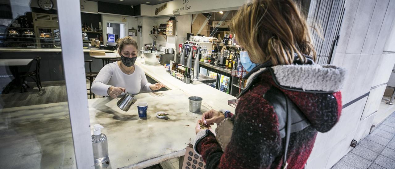 Vanesa García sirve un café para llevar a una cliente en la calle Ventura Rodríguez.