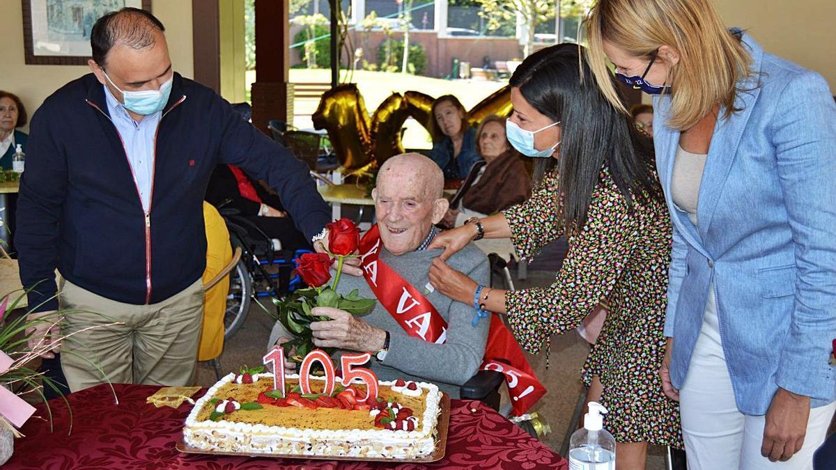 Constantino Freire sopla las velas de su 105 cumpleaños junto a la alcaldesa y la delegada territorial.    // D.P.