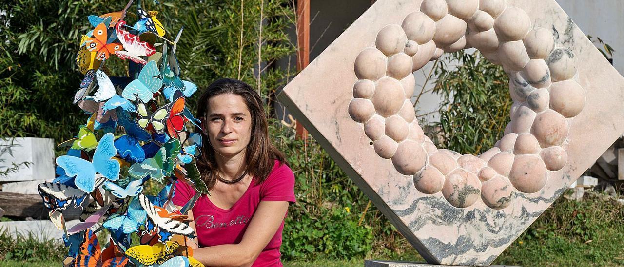 La escultora búlgara Liliya Pobornikova, afincada en Tomiño, con las mariposas de hierro y otra de sus creaciones.
