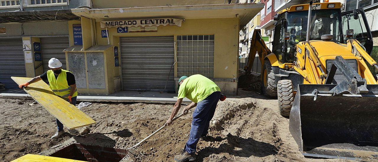 Operarios realizan ayer parte de los trabajos de cubrición de las catas arqueológicas del Mercado Central.   MATÍAS SEGARRA