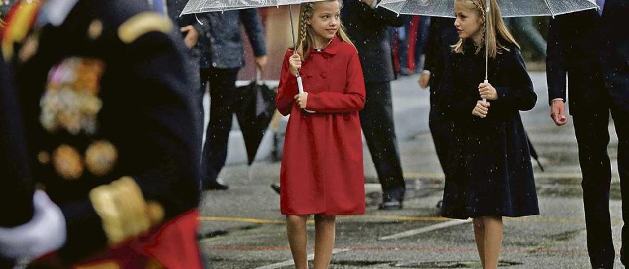 La Princesa de Asturias, Leonor de Borbón, a la derecha, y su hermana Sofía, protegiéndose de la lluvia con los paraguas en el desfile de la Fiesta Nacional el año pasado.