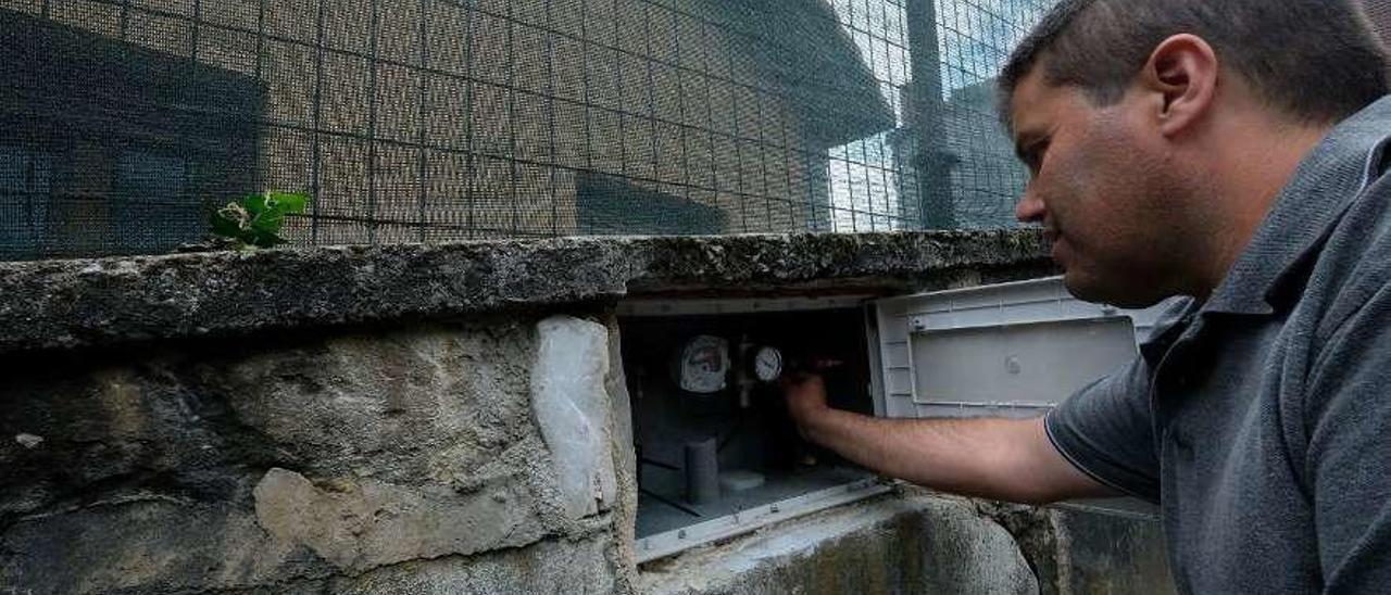 Germán González, comprobando el filtro de su contador. Arriba, los restos del reptil que encontró en el circuito que abastece su vivienda, en Soto .