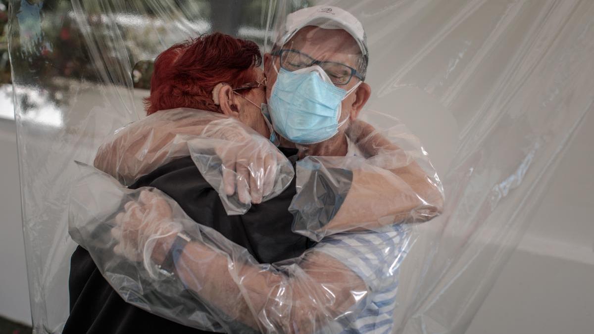 Una interna en una residencia de mayores valenciana abraza a su sobrino a través de un plástico.