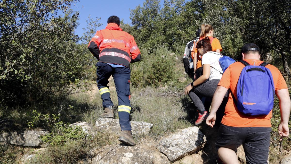 Pla mitjà on es poden veure voluntaris i Bombers participant en la recerca d'un menor desaparegut al nucli de Llanera, a Torà, el 12 d'octubre de 2021. (Horitzontal)
