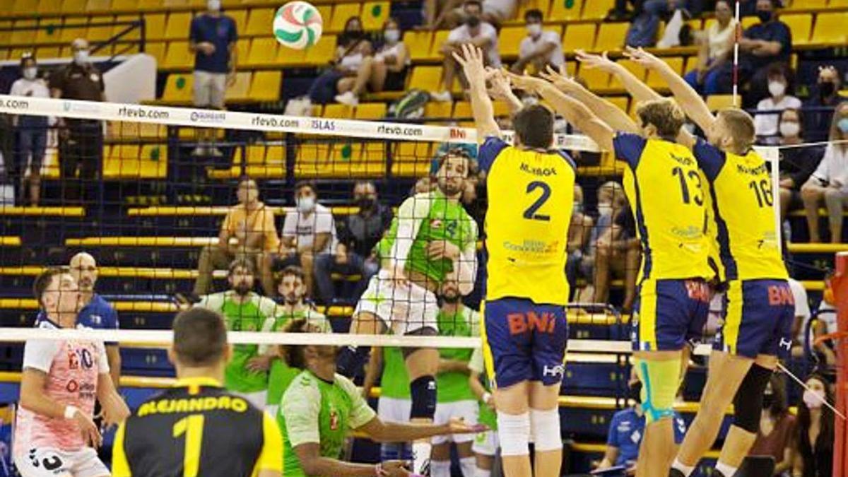 El receptor Juanmi González trata de superar el triple bloqueo del Club Voleibol Guaguas.