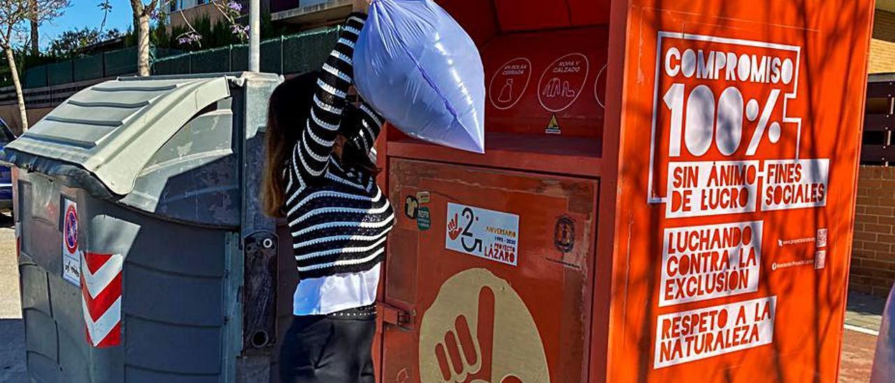 Una mujer deja ropa en un contenedor de Proyecto Lázaro.  | RAFA ARJONES