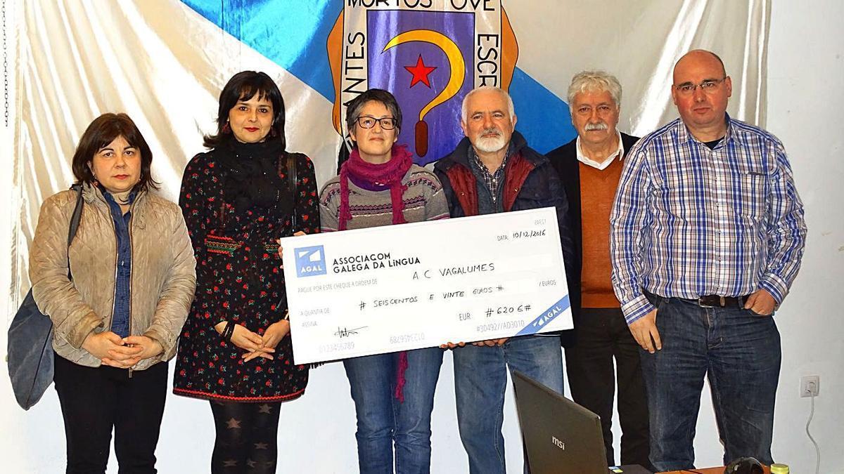 Membros de Vagalumes ao recibir unha doazón dos beneficios dun libro de Susana Aríns.  | // VAGALUMES