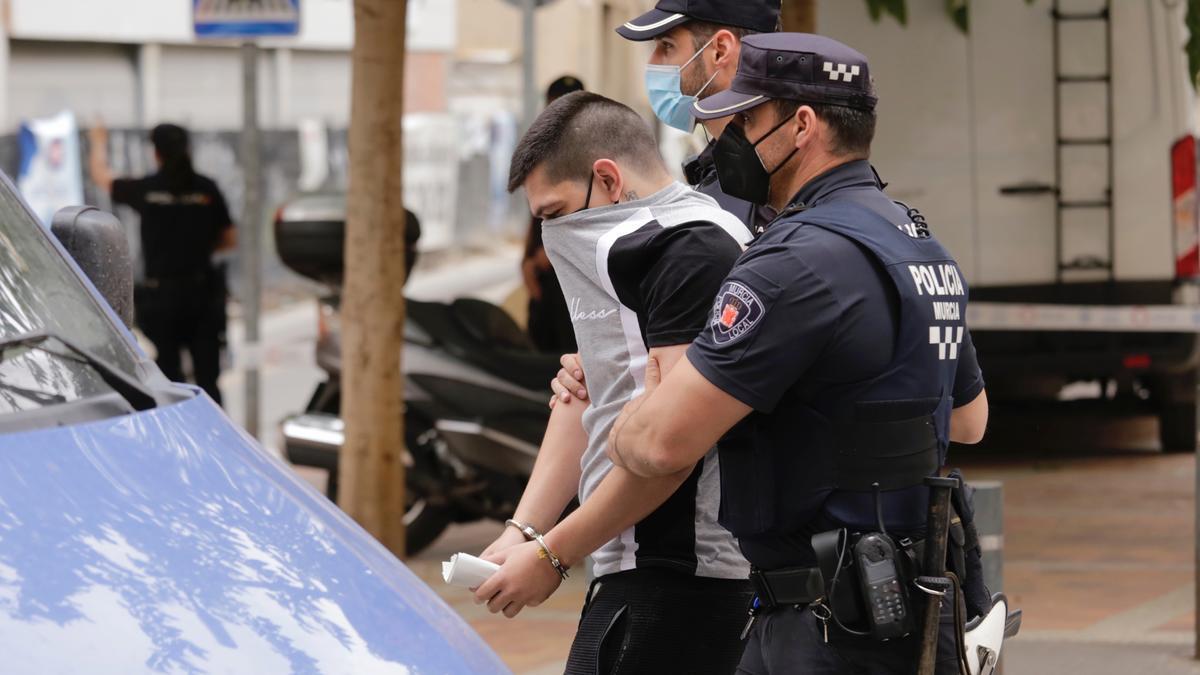 Dos agentes trasladan al sospechoso, esposado, desde el edificio hasta el vehículo policial.