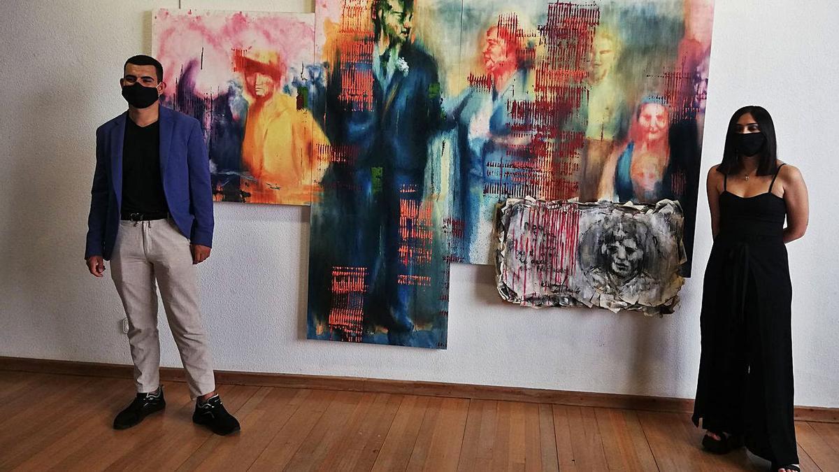 Manuel Vergel y Daniela Somoza, comisaria de la exposición, posan junto a uno de los cuadros.  | I. F.