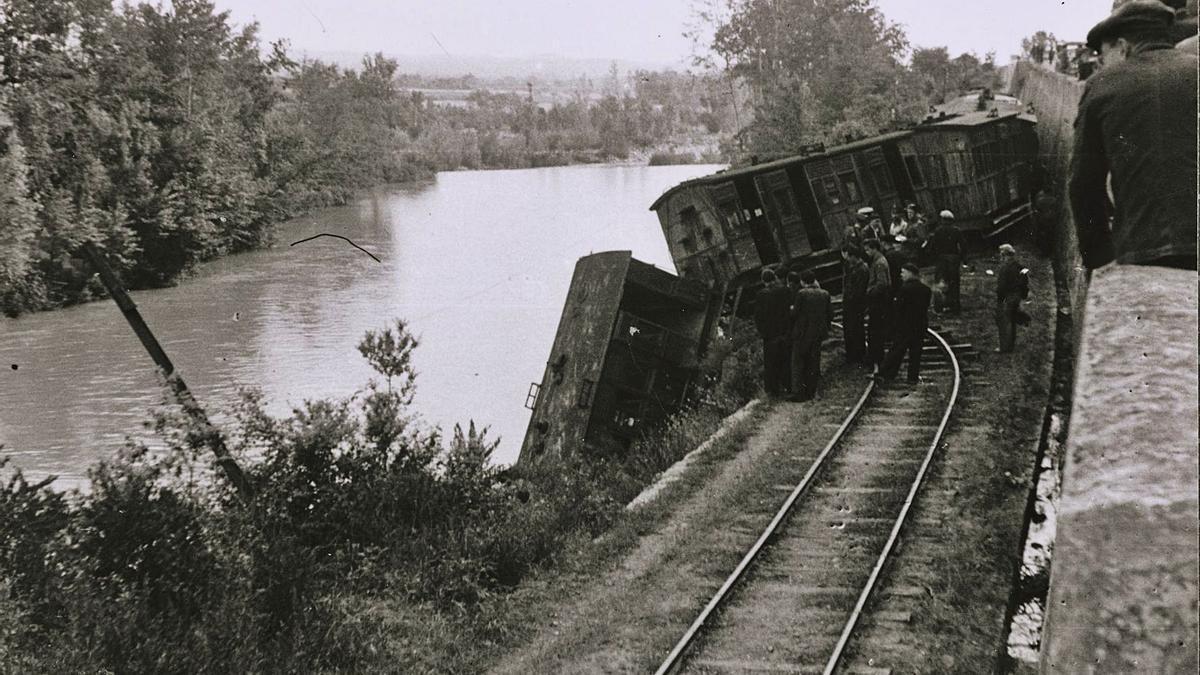 Un grup de persones sobre les vies, desviades cap al riu Ter, i al seu darrere els vagons del comboi descarrilat, poc després de l'accident.