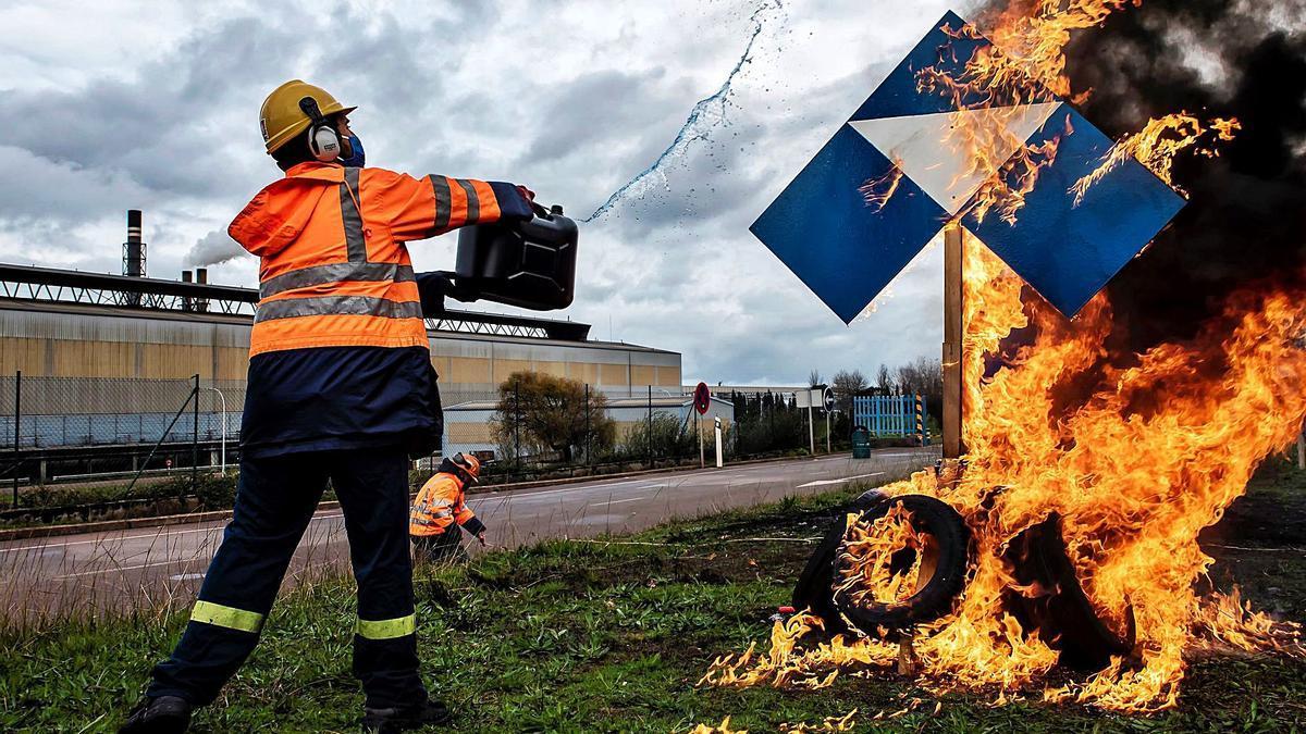 Un trabajador de Alcoa San Cibrao echa gasolina a un cartel de la multinacional, en una barricada ante la fábrica. |   // EMILIO PÉREZ VÁZQUEZ/EFE