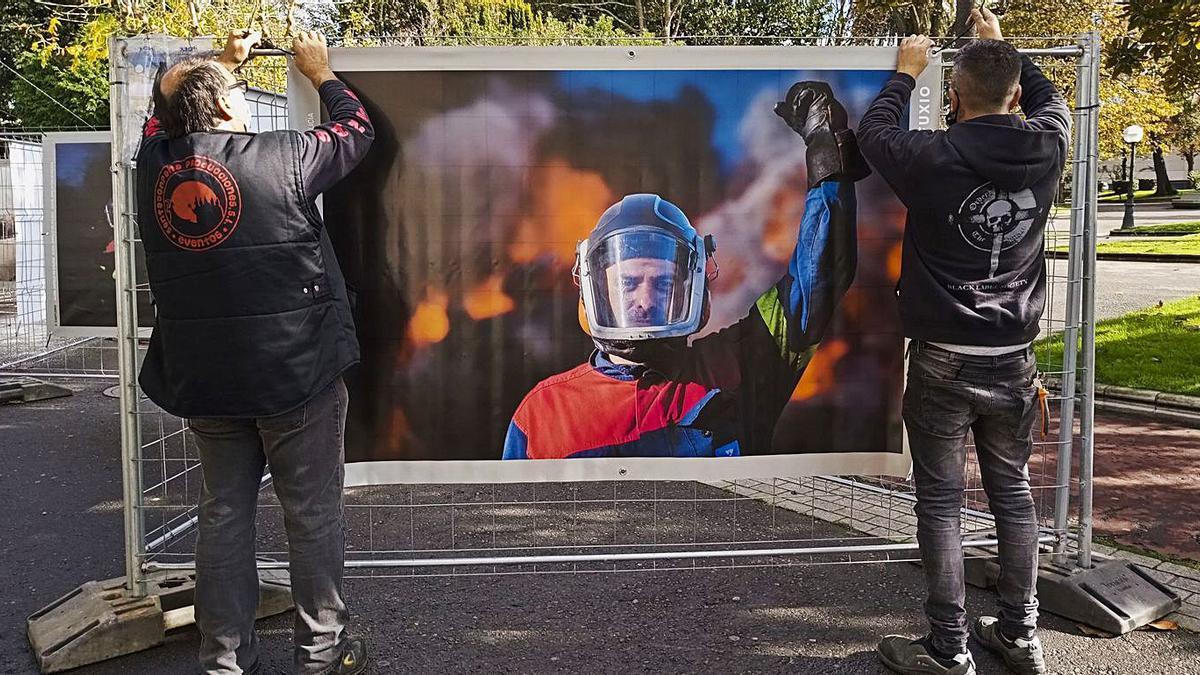 Dous traballadores colocan unha foto de Vanessa Casteleiro nos xardíns, na mostra 'Expolio' .     // CASTELEIRO
