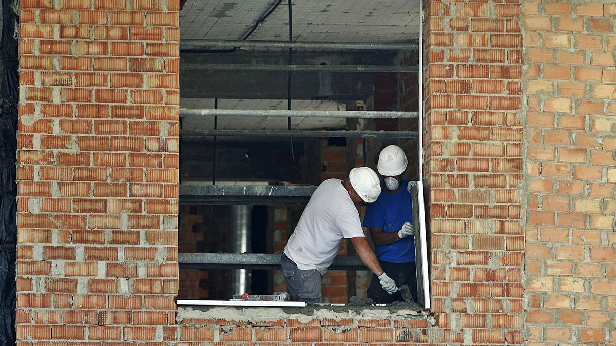 Trabajadores en la obra de construcción de un edificio de viviendas en Málaga.