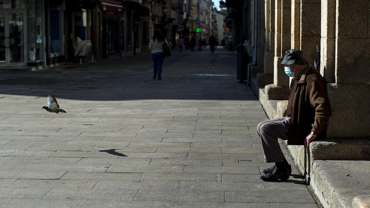 Un hombre descansa en una plaza de O Carballiño completamente vacía