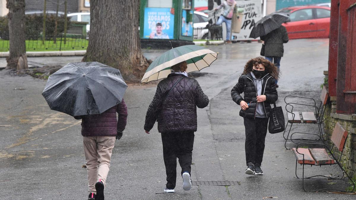 Varias personas con paraguas en un parque de A Coruña.