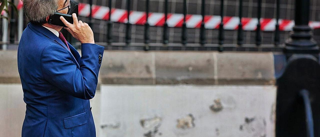 El  consejero de Hacienda, Román Rodríguez, habla por teléfono en el patio en obras del Parlamento. | | MARÍA PISACA