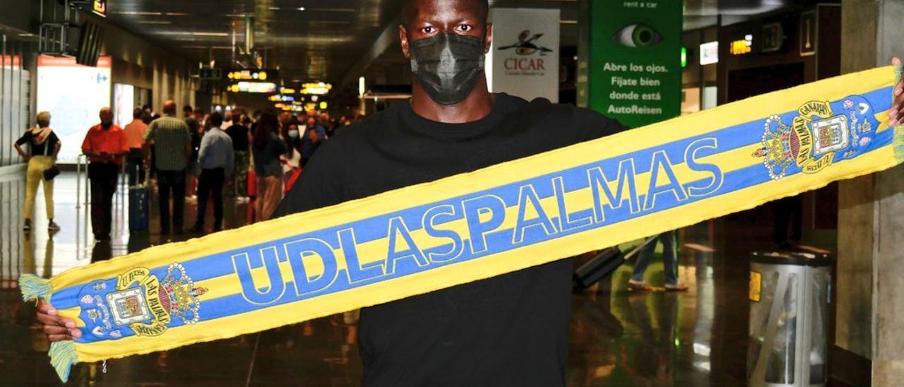 Mfulu posa con la bufanda de la UD esta mañana en el aeropuerto de Gando