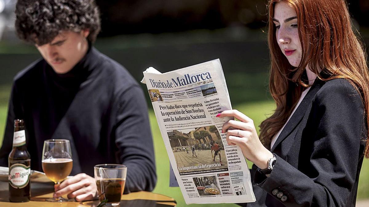 Una pareja lee Diario de Mallorca en una terraza.