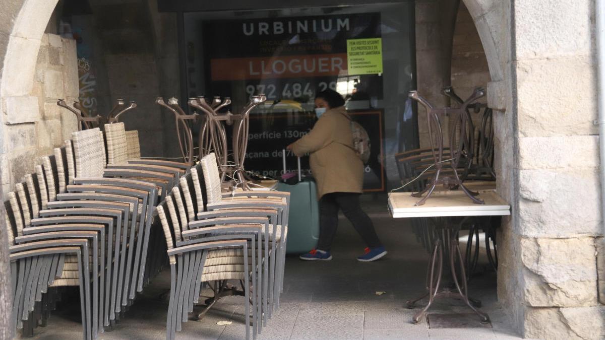 Les cadires d'un bar tancat apilades a causa de l'obligatorietat de tenir tancat.