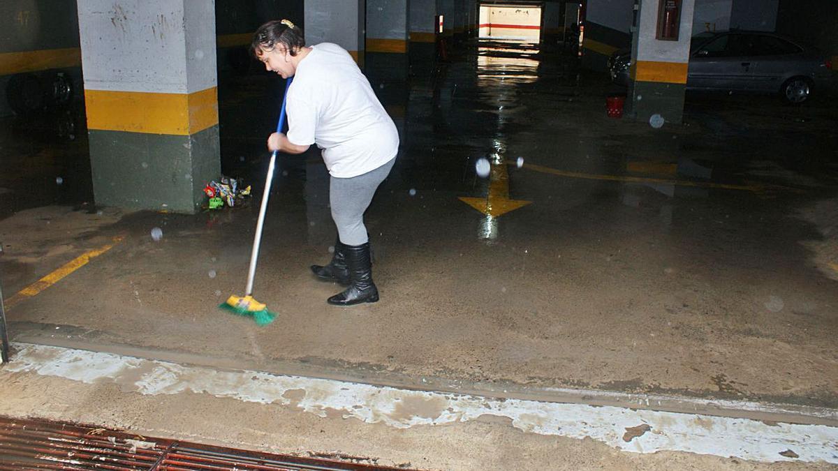 Una mujer achica agua  en uno garaje inundado en la urbanización Reina Mercedes.  |