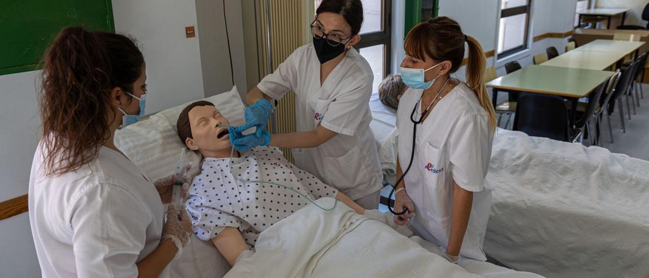 Dos alumnas de grado medio de Enfermería asisten a una clase en la escuela CEDESCA de Barcelona, que acaba de cumplir 40 años.