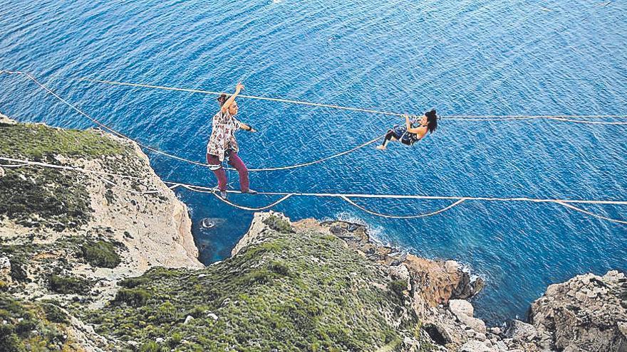 Jóvenes equilibristas caminan sobre la cuerda floja en los acantilados de Moraira