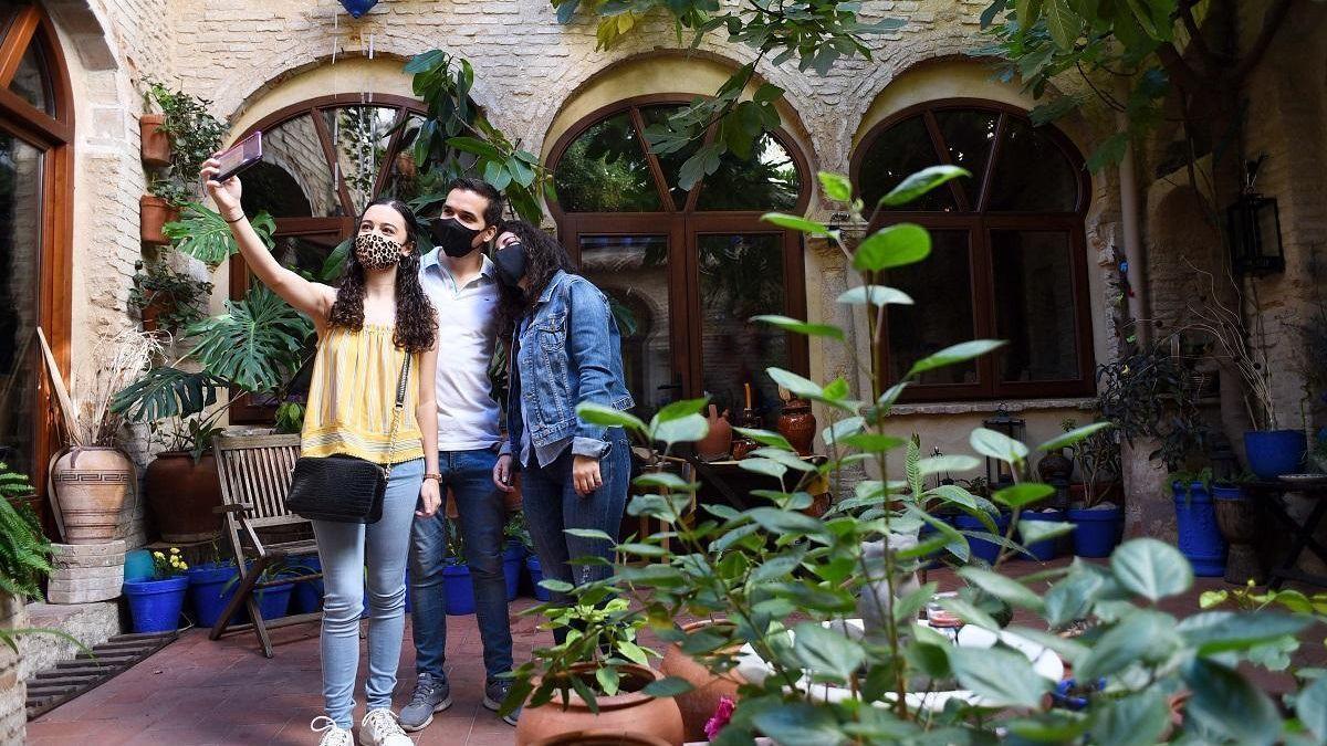 Varias personas se fotografían en un patio de Córdoba durante su visita.