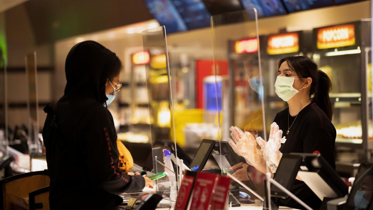 Una mujer compra una entrada de cine en California.