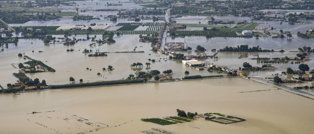 Dos guardias civiles y un policía cooperan en la evacuación de una mujer afectada por la devastadora inundación.