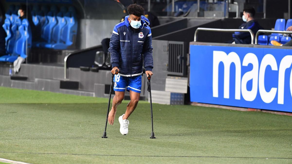 Derik, camina ayer con muletas en Riazor después de lesionarse.
