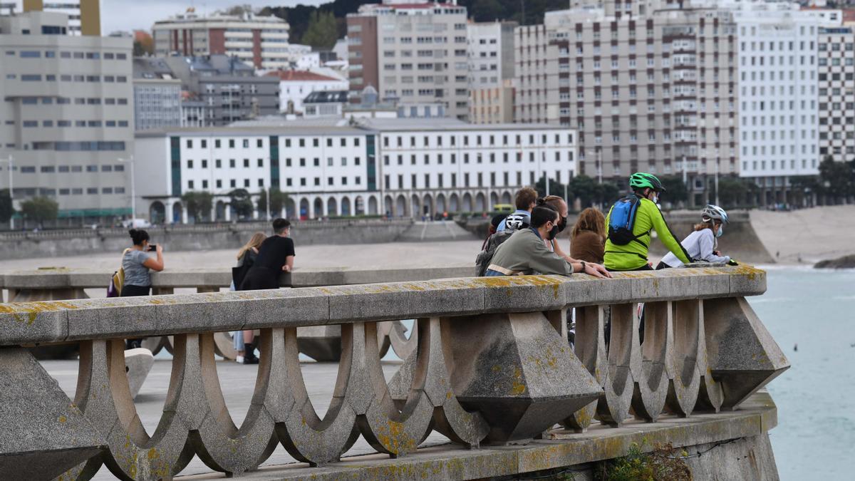 Varias personas con mascarilla en el paseo marítimo de A Coruña.