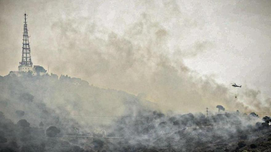 Setze dotacions i un helicòpter treballen en un incendi forestal a la serra de Collserola